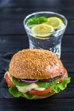 柠檬水用在黑木桌上的素食者汉堡 库存图片