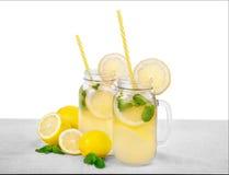 柠檬水的两个巨大的金属螺盖玻璃瓶从新鲜薄荷叶子,水和汁液柠檬的,隔绝在白色背景 库存照片
