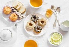 柠檬绿茶和甜点-香蕉松饼、曲奇饼用焦糖和坚果,油炸圈饼用巧克力和柠檬釉,茶具在丝毫 免版税库存照片