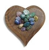 查克拉水晶翻滚了在木心脏匾的石头 免版税库存照片
