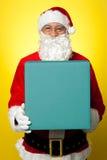 查出的微笑的圣诞老人藏品礼物盒 免版税库存照片