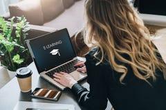 查出的背面图白色 少妇研究有题字的膝上型计算机在屏幕方形的学术盖帽的电子教学和图象 免版税图库摄影