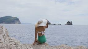查出的背面图白色 年轻人在泳装和一个宽帽子打扮的相当被晒黑的妇女,享有生活坐岩石和看  股票录像
