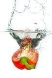 查出的辣椒粉红色飞溅水白色 免版税库存照片