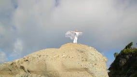 查出的黑色概念自由 妇女白色礼服的和有站立在岩石的围巾的 跳舞 飞行 移动 股票录像