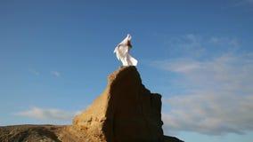 查出的黑色概念自由 妇女白色礼服的和有站立在岩石的围巾的 跳舞 飞行 移动 股票视频