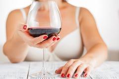 查出的om红色waite酒 喝红葡萄酒的妇女在卧室 奶油被装载的饼干 免版税库存照片
