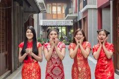 查寻在兴奋,小组的惊奇的愉快的美女看某事的妇女佩带的cheongsam chainese礼服 免版税库存照片
