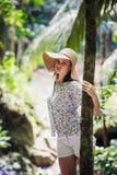 查寻在森林的草帽的愉快的少妇 免版税库存照片