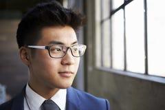 查寻在窗口,关闭外面的年轻亚洲商人 图库摄影