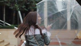 查寻天空和举手的英俊的年轻女商人为检查是否雨中止 她微笑和接近 股票视频
