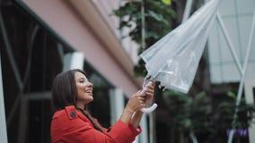 查寻天空和举手的英俊的年轻女商人为检查是否雨中止 她微笑和接近 股票录像