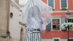 查寻天空和举手的英俊的年轻女商人为检查是否雨中止 她微笑和接近 影视素材
