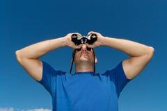 查找与双筒望远镜的年轻人 免版税库存图片