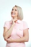 查找中年美丽的妇女认为和作梦在白色背景 库存图片