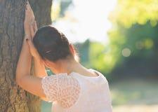 查找从结构树的女孩。 背面图 免版税库存照片