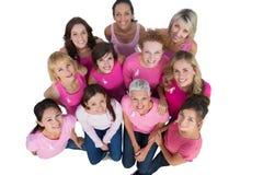 查找佩带的桃红色的快乐的妇女为乳腺癌 免版税图库摄影