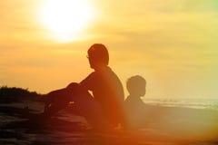 查找儿子日落的父亲 免版税库存图片