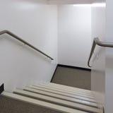 查找在与扶手栏杆的一个明亮的楼梯下 免版税库存图片
