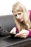 查找在片剂个人计算机的长沙发的妇女 免版税库存照片