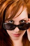 查找在红头发人太阳镜的美丽的夫人 库存图片