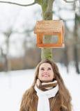 查找在结构树的鸟馈电线的愉快的少妇 免版税库存照片