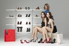查找坐三名尝试的妇女的鞋子新 免版税库存照片
