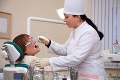查找她的患者的牙科医生 免版税库存照片