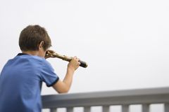 查找望远镜的男孩 免版税库存图片