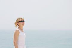 查找海洋的白肤金发的蓝色女孩 免版税图库摄影