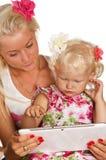 查找片剂的母亲和女儿 库存照片