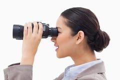 查找通过双筒望远镜的女实业家 库存照片