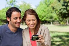 查看在照相机的妇女和她的朋友照片 免版税库存照片