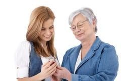 查看在移动电话的母亲和女儿照片 免版税库存图片