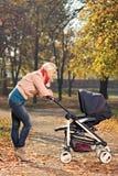 查看她的婴儿推车的一个新母亲婴孩 库存照片