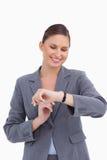查看她的手表的微笑的女实业家 库存图片