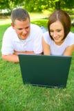 查看有微笑的夫妇膝上型计算机 免版税库存图片