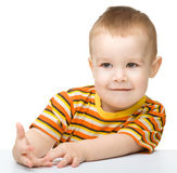 查看某事的一个逗人喜爱的小男孩的纵向 库存照片