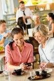 查看照片咖啡馆的母亲和女儿 免版税库存照片