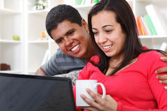 查看膝上型计算机的愉快的夫妇 免版税库存照片