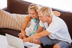 查看膝上型计算机的愉快的新夫妇 库存照片