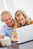 查看膝上型计算机的愉快的新夫妇 免版税库存照片