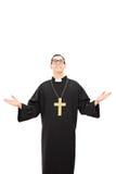 查寻一位年轻的天主教教士的垂直的射击 免版税库存照片