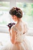查寻一件豪华的礼服的美丽的迷人的新娘 坐在婚礼礼服的愉快的新娘画象在一个白色照片演播室 免版税库存照片