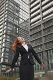 查寻与风的激动的年轻女实业家吹在她的头发 免版税库存照片