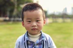 查寻和害羞地微笑在公园的小中国美丽的男孩 免版税库存照片