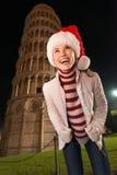 查寻在比萨斜塔附近的圣诞老人帽子的妇女 免版税库存图片