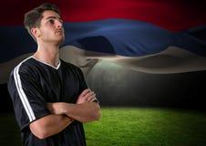 查寻在领域的足球运动员,与后边旗子 库存照片