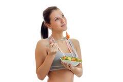 查寻并且吃新鲜蔬菜沙拉一个年轻逗人喜爱的女孩的水平的画象 库存照片
