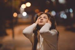 查寻年轻情感的妇女,城市街道在夜,平衡点燃bokeh背景户外 库存图片